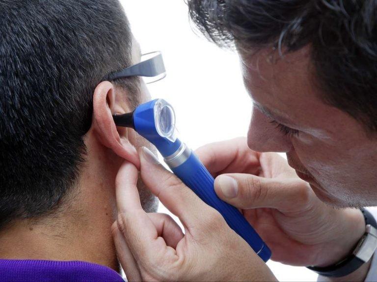 Bác sĩ nhìn ống tai ngoài qua đèn soi tai