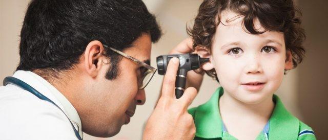 Bác sĩ dùng đèn soi tai kiểm tra tai cho trẻ
