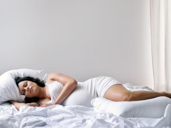 Để giảm bớt chuột rút, bạn có thể nằm nghiêng, gập đầu gồi và đặt gối ôm giữa 2 chân