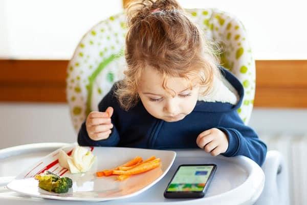 Không nên cho trẻ dùng thiết bị điện tử khi ăn